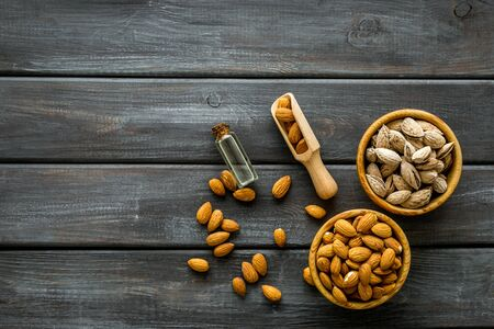 Healthy snack with almonds and oil on wooden background top view mock up