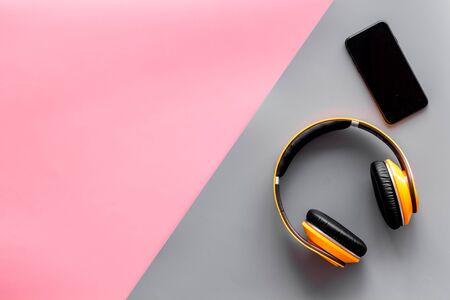 Telefono cellulare e cuffie wireless come gadget per ascoltare la musica su sfondo rosa e grigio vista dall'alto mockup Archivio Fotografico