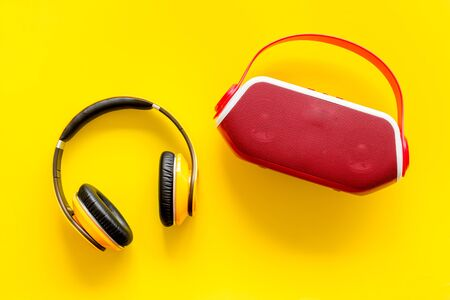 Audio listening with wireless headphones and portable speakers on yellow background top view