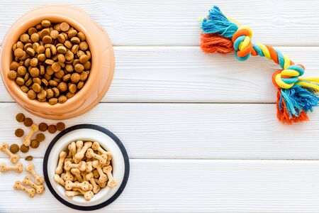 Puppy dry food in bowl and toys on white wooden background top view copyspace