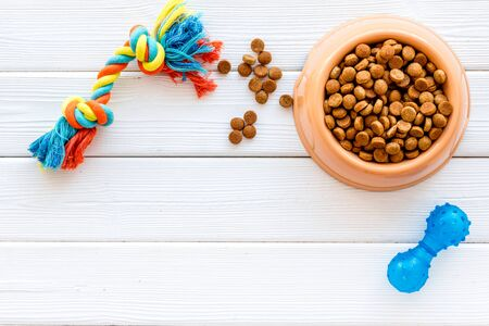 Dog dry food in bowl and toys on white wooden background top view space for text