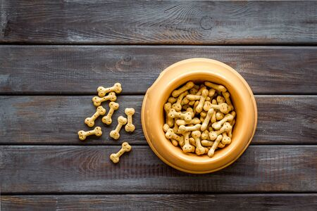 Pet dry food in bowl on wooden background top view