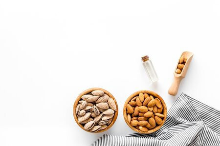 Almond oil in bottle with almonds on white background top view copyspace