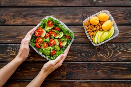 to-go box with salad and fruit in hands for lunch on wooden background top view