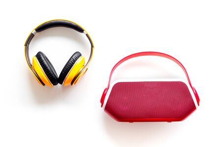 Wireless speaker and headphones as music gadgets on white background top view