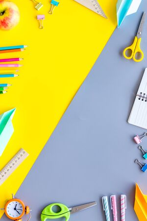 Creative mess on students desk on yellow and gray background top view mockup