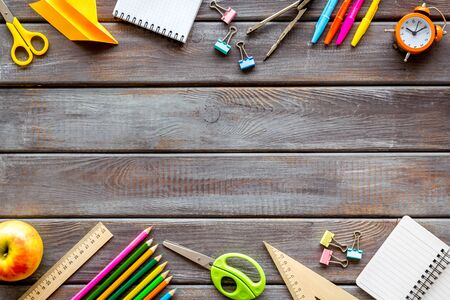 Creative mess on students desk on wooden background top view mock up