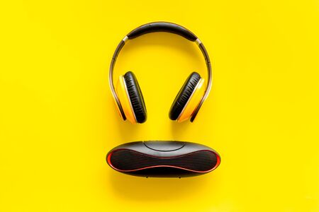 Portable wireless speakers and headphones as gadgets for listen to the music on yellow background top view