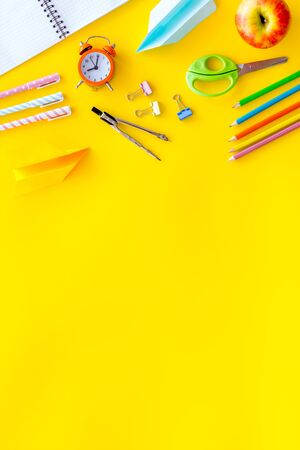 Creative mess on students desk on yellow background top view mockup