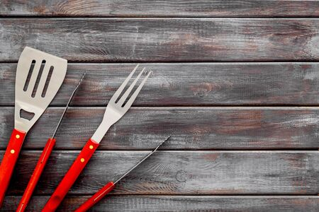 spatula, fork, tongs for barbecue on wooden background top view mock up