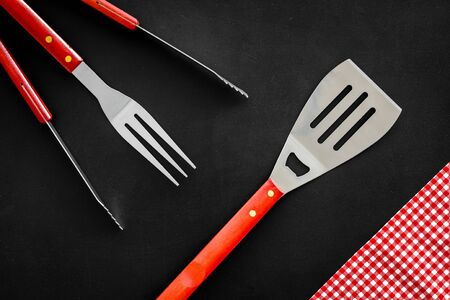 spatula, fork, tongs for barbecue on black background top view