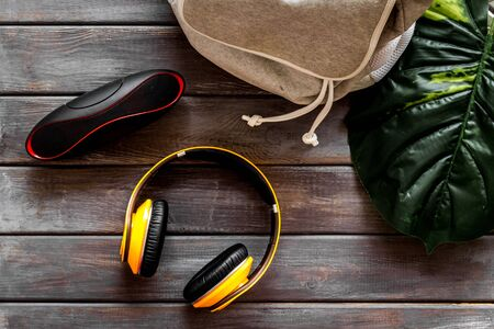 Audio listening with wireless headphones and portable speakers on wooden background top view