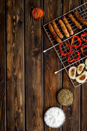 barbecue, sausages, vegetables on wooden background top view space for text