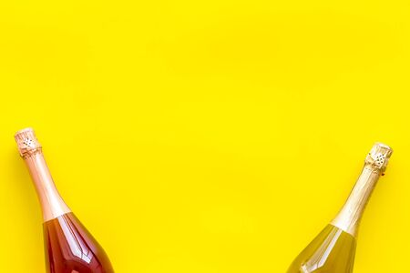 Party concept with champagne bottle on yellow background top view copyspace