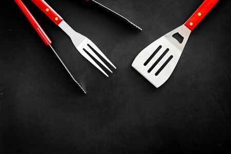 spatula, fork, tongs for barbecue on black background top view mock up
