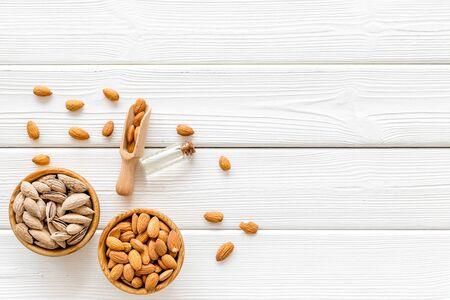 Healthy snack with almonds and oil on white wooden background top view mock up 写真素材