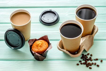 Coffee cups with muffin and coffee beans. Coffee to go on mint green wooden background