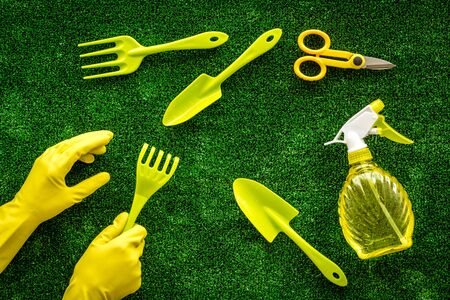Rake, spade, scissors, hands in gloves. Instruments for gardener on green grass background top view pattern Stockfoto - 128552046