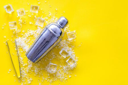 Pile of ice cubes and shaker on yellow bar desk background top view space for text