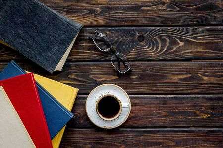Books on library desk for reading, coffee, glasses on wooden background top view mockup