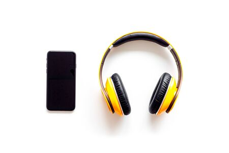 Mobile phone and wireless headphones as gadgets for listen to the music on white background top view