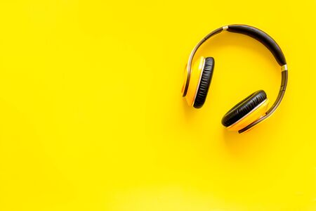 Audio listening with wireless headphones on yellow background top view space for text