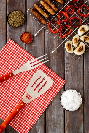 barbecue, sausages, vegetables and kitchen tools on wooden background top view Imagens