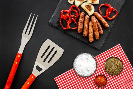 barbecue, sausages, vegetables and kitchen tools on black background top view
