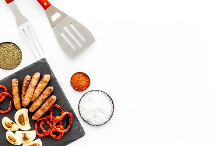 barbecue, sausages, vegetables and kitchen tools on white background top view mock-up.