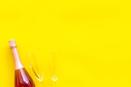 Festive and celebrate. Party with champagne bottle and glasses on yellow background top view space for text Stockfoto