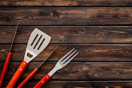spatula, fork, tongs for barbecue and sausages on wooden background top view mock-up.