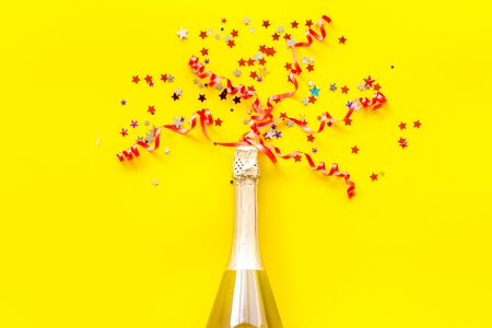 Alcohol for party. Champagne bottle with colorful party streamers for celebration on yellow background top view