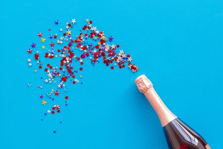 Festive and celebrate. Party with champagne bottle and colorful party streamers on blue background top view