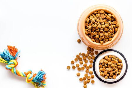 Cat and dog dry food in bowl and toys on white background top view mockup Stock Photo