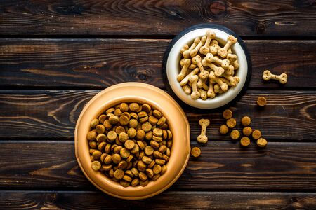 Dog dry food in bowl on wooden background top view