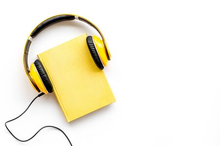 Listening audio books with headphones in library on wooden background top view space for text