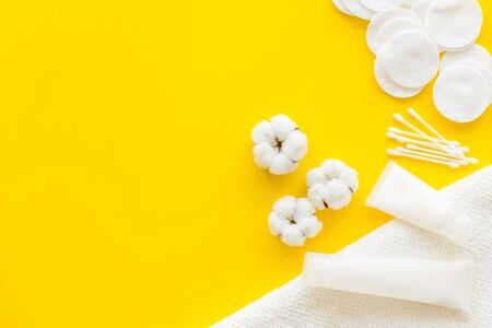 Hygiene cotton swabs, pads and cream for pattern on yellow background top view mockup