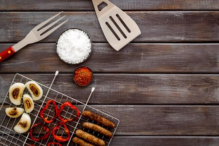 barbecue, sausages, vegetables and kitchen tools on wooden background top view copyspace