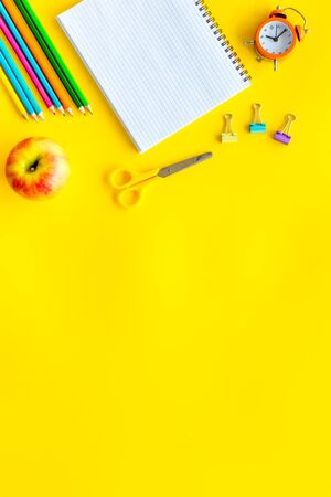 Education mockup with pupils stationery, clock, apple and textbook on yellow background top view 版權商用圖片