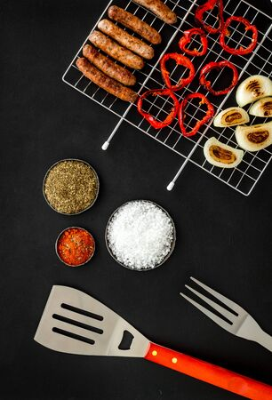 barbecue, sausages, vegetables on black background top view Imagens