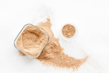 Sports nutrition with scoop and protein on white background top view