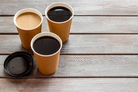 Café para llevar en vasos de papel con tapas en el espacio de fondo de la mesa de madera para texto Foto de archivo