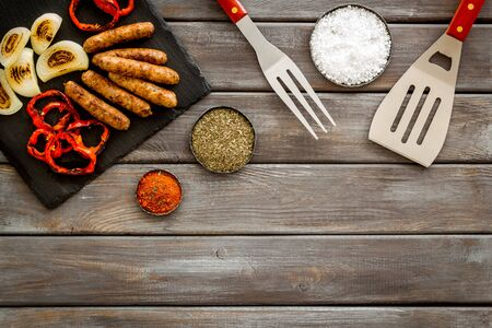 barbecue, sausages, vegetables and kitchen tools on wooden background top view mock up Imagens