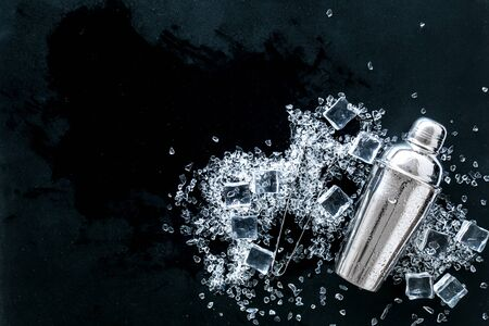 Pile of ice cubes and shaker on black bar desk background top view space for text
