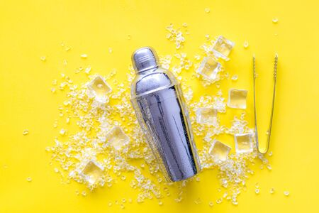 Pile of ice cubes and shaker on yellow bar desk background top view