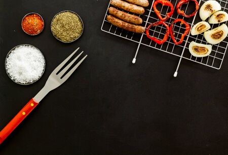 barbecue, sausages, vegetables on black background top view mockup Imagens