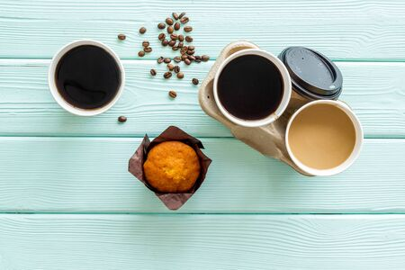 paper cups with black coffee and cappuccino to take away, beans, muffin on mint green woodne background top view