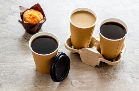Coffee to take away in paper cups with muffin on gray table background