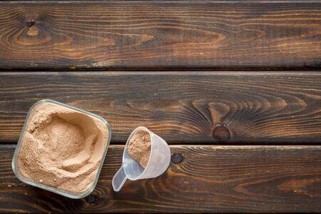 Sport diet with protein powder on wooden background top view copyspace