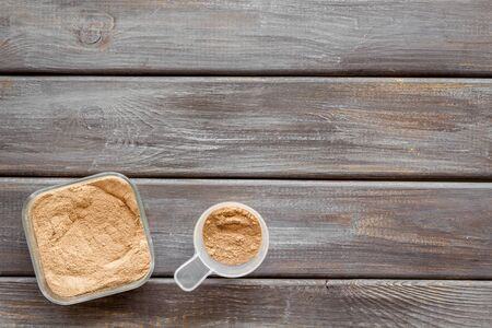 Nutrition for workout with protein cocktail powder on wooden background top view mockup